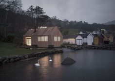 Koreo Arkitekter and Kolab Arkitekter have transformed an old boathouse on Norway's west coast into a summerhouse that becomes a glowing beacon by night