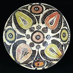 Nishapur bowl decorated with palmettes and roundels    Iran, 10th century      the bowl on raised foot with straight sides and slightly inverted rim of red clay covered in white slip painted with alternating palmettes in incised black, olive green and red slips separated by roundels accentuated with white dots  22cm diameter