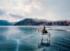 Horse riding on ice of lake Baikal, Siberia, Russia. What a pic!