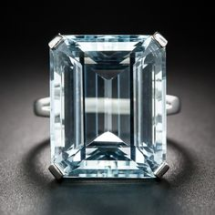 Vintage Aquamarine Ring. A cool glacial blue emerald-cut aquamarine, weighing 23.50 carats, glistens solo from within a hand fabricated, gleaming white gold mounting in this bright and beautiful just-for-fun-ring, dating from the mid-twentieth century. The aqua measures 3/4 by 5/8 inch.
