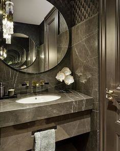 We love a bit of drama in a guest bathroom, here with marble slabs over textured wallpaper and round mirrors on both walls . - Amanee Ammar - We love a bit of drama in a guest bathroom, here with marble slabs over textured wallpaper and roun - Bad Inspiration, Bathroom Inspiration, Bathroom Design Luxury, Modern Bathroom, Stone Bathroom, Industrial Bathroom, Guest Toilet, Circular Mirror, Bathroom Layout