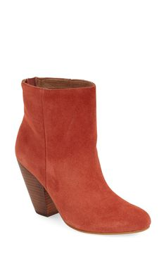 This shapely, round-toe bootie in brick suede gets a boost from a stacked, cantilevered block heel for a retro-chic look.