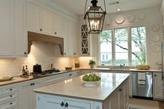 true {kitchen} love!  that lantern, the wood detail above the range, the collection of white plates.  so pretty!