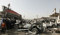 People gather at the site of a car bomb attack at car dealers' shops in Baghdad March 7, 2014. At least 26 people were killed in Iraq on March 6, 2014 as insurgents set off roadside bombs and detonated explosives-packed cars in Baghdad and elsewhere, police said.