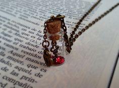 Colgante botellita de cristal, con una llave dentro y purpurina de estrellitas rojas, en el exterior un charm de corazón con una cerradura.