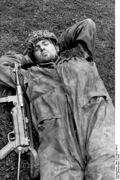 German paratrooper taking a nap with his MP 40 submachine gun at his side, Normandy, France, 1944.