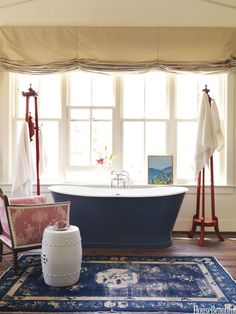 Santa Ynez, CA -designer Mary Watkins Wood used rug instead of bath mat. Rugs are made to withstand more wear than the occasional wet foot!  Waterworks Candide tub painted in Dunn-Edwards Slate. Chair covered in Scalamandre Feng Shui. Mecox ceramic garden seat.