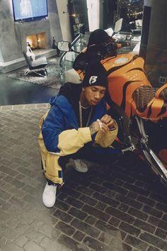 Tyga wearing  Supreme Ruff Ryders Beanie, Tommy Hilfiger Vintage Windbreaker Jacket, Vans Authentic Sneaker, Saint Laurent Ripped Jeans
