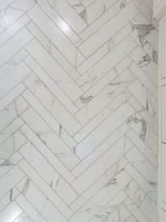 white carara marble and accents in a herringbone pattern.