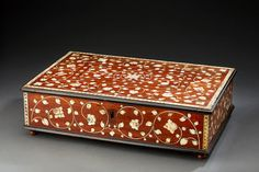 Mahogany cabinet inlaid with ivory, decorated with rosettes in frames with foliage foliage. It is decorated with five faces. The flap conceals six traps with two covers and a row of four drawers hiding secret drawers. Indo-Portuguese work of the eighteenth century.