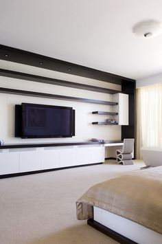 For a tv in the bedroom... add floating shelves around the tv to anchor it and to divide attention away from it.