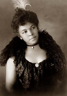 This is a portrait of a young African American woman. The photograph was taken in 1899. So many of the pictures of African Americans from this era are in the context of sharecropping and other more unfortunate circumstances. While we don't have any other details on this photograph, it appears that this woman, and her family have done better than what was typical for African Americans of this time.