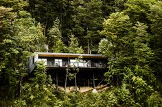 A vacation home for a Chilean family rises on stilts from a rocky cliff, enjoying idyllic views of Lago Todos los Santos.