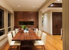 Nice painted ceiling with flush recessed lights, brown wood on the cabinets along with the rectangular dining table, wooden frame chairs upholstered with with foam & white leather then a shiny hardwood floor.