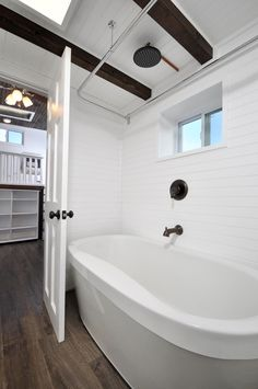 Past the kitchen is the luxurious bathroom with oval soaking tub and rain shower head, sink and vanity, and composting toilet.