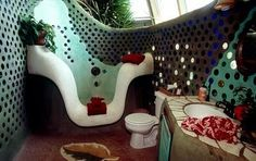 """Earthship, bathroom (2 of 4). Earth-rammed walls and floors (made of either compacted """"earth"""": dirt, sand, and sometimes cement; or with a collection of recycled old tires packed with earth) supports holding in the thermal heat collected from the passive solar. Windows are placed on sun-facing walls which admit lighting and heating (""""passive solar""""). These large passive solar windows are also generally used to provide lighting for an indoor greenhouse. Earthships are often horseshoe-shaped…"""