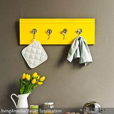 Das gelb angestrichene Holzboard fungiert als DIY-Hakenleiste für Küchenutensilien. Besonders fantasievoll: die verbogenen Löffelchen, die als Haken dienen.…