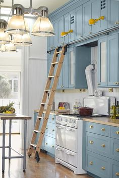 Double-height cabinets, accessed by a ladder on wheels, maximize wall space.