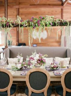 I love the flowers hanging ABOVE the table.  That way you get the tall visual interest without blocking sight lines from tall centerpieces.  I'd even add some twinkle lights for evening romance.