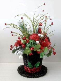Christmas decor centerpiece in snowman black snowman hat is filled with artificial greens, sheer wired ribbon, glitter Christmas balls, berries. Festive table decoration for the Christmas holidays and parties Measures: 24 in H x 15 in W For more christm Noel Christmas, All Things Christmas, Christmas Wreaths, Christmas Ornaments, Christmas Balls, Christmas Flower Arrangements, Christmas Table Decorations, Floral Arrangements, Snowman Decorations