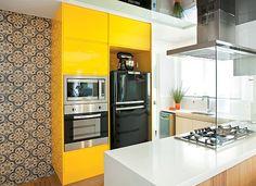 """O armário com laca brilhante amarelo gema deu o ar moderno à cozinha que é aberta para a sala. """"É uma cor divertida que faz uma contraposição equilibrada com o aço inox e o preto dos eletrodomésticos"""", diz a arquiteta Beatriz Quinelato."""