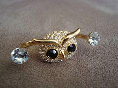 Anel duplo em metal dourado no formato de coruja com um cristal Swarovski de cada lado. Aplicação de strass branco e preto na coruja.  Ambos os aros são tamanho 21 (diâmetro: 1,88cm) R$52,00