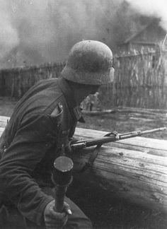 German infantryman armed with a kar 98 is ready to throw his stick grenade. If he has pulled the ring the fuze is burning...