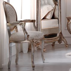 The Luxurious Rococo Upholstered Antiqued Armchair is shown here in an antiqued silver finish with accents of gold and champagne with matching piping to complement the beautiful mink patterned fabric. A statement chair for any room in the house.