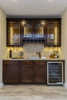 Custom lower level bar design features wood look low maintenance flooring, custom cabinetry, LED cabinet lighting, can lights in the ceiling, glass front cabinet doors, wine refrigeration, a deep stainless steel sink with oil rubbed bronze pullout faucet