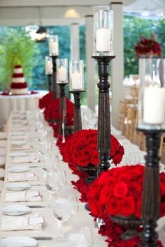 Beautiful red fresh roses and tall wooden candle holders used as wedding long table centerpieces. Red wedding ideas