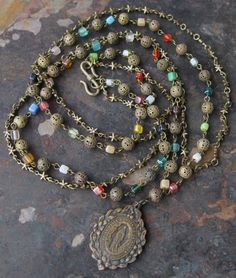 Diocesains Long Necklace of Vintage Beads Brass Chain and Vintage French Religious Medal Multicolor with Stars. $38.00, via Etsy.