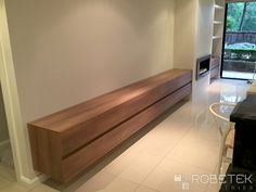 CUSTOM LIVING ROOM STORAGE These wall hung units are made in Polytec Sepia Oak which gives a beautiful warmth to the room.