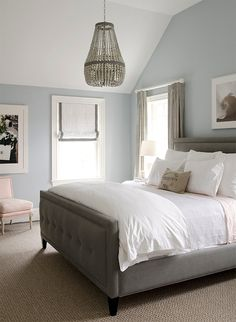 Gorgeous bedroom with blue walls paint color, gray linen tufted bed, crisp white bedding, pink sheets, Ro Sham Beaux Malibu Up Chandelier, white roman shades with gray ribbon trim, pink French chair and gray curtains window panels.