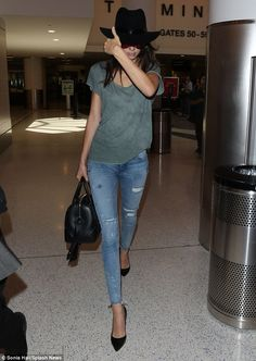Not very model-like! Kendall Jenner gets camera shy as she strides through LAX showing off her slim pins in skinny jeans | Daily Mail Online