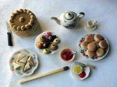 Tea time food in miniature. The matchstick shows the scale. The teapot, crockery and knives are all polymer clay as well as the food.