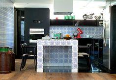 A ilha central desta cozinha, toda de azulejo estilo português, tem apoio para o preparo das refeições e para o fogão