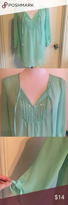 Express Sequin Detail Blouse in Mint Beautiful flowy blouse from Express in a gorgeous mint green (kind of aqua) color. 3/4 sleeves are slightly rolled. Ties detail at Neck and sequins down front. Flowy and semi-sheer. So comfy, flattering and cute! Fits true to size (I wore as a size 6 and a size 8). Feel free to ask questions! Also available in coral! :) There are some small black marks on the sleeve, not very noticeable when on. I haven't tried anything specific to remove them. Express…