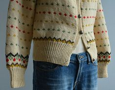 This handknit wool fair isle cardigan will keep you warm and toasty through all the chilly days ahead. Beautifully knit rounded yoke pattern in shades of bright red, olive green, antique gold and deep chocolate brown are set against a cream background. Striped birdseye pattern in red,