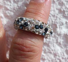 Ein Edelstahlring in Größe EU 12.Bei diesem Ring wurden zur Veredelung Kristalle der Marke Swarovski ELEMENTS in einem Mix aus schwarz und silk verwendet.Ei