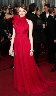 Emma is wearing a red halter Giambattista Valli gown with bow detail on the halter. Nicole Kidman wore this exact gown too. In my opinion both look amazing in it. I love the red color and the bow on the halter.