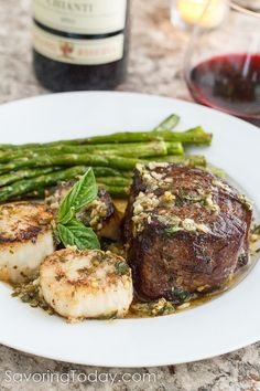Tenderloin steak and scallops with scampi sauce on a white plate with asparagus set in front of a bottle of wine and glass.