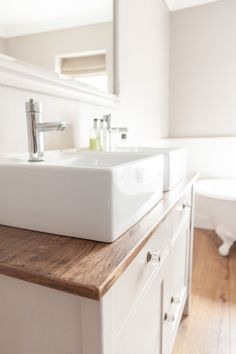 Wooden top below sink? Moving storage to under sink would give a feeling of more space without a cabinet on the wall.