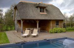 Eikenhouten poolhouse met rieten dak, overdekt terras met terrasverwarming, bar, badkamer en toilet. Bovenverdieping met eikenhouten massief parketvloer