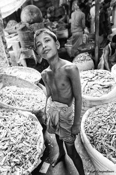 Bangladeshi boy among big sackcloth bags full of dry fish for sale at the Karwan Dry Fish Market (Bazar), Dhaka, Bangladesh, Indian Sub-Continent, Asia. Black and White Photography.