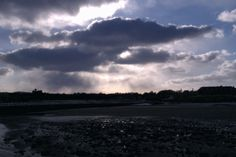 Dark clouds and sunshine battle it out over The Old Course in St Andrews. 11 March 2013.