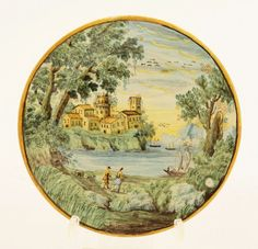 Castelli maiolica Plate, c.1730, painted with a castle on a promontory above shipping on a lake, two figures in the foreground, 17.7cm