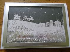 "Christmas winter scene on Craftsuprint created by Karen Faulds - I cut the background from  dark blue pearlescent paper and the rest of the layers from ""iced silver"" pearlescent paper.I stuck all the layers in order and flat (ie not using foam squares or silicon) onto a matching iced silver A5 card.I cut a frame from linen effect silver card, attached clear acetate to the back and then attached over the top of the card using foam tape all the way around, with silver glitter behind to make a…"