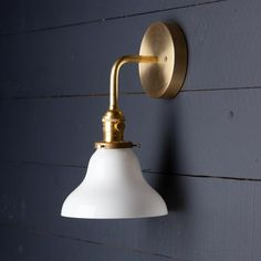 This Milk Glass Bell Shade Brass Wall Sconce fixture features-Raw Brass Mount-Raw Brass Bent Arm-Raw Turned Brass Socket with Switch-7in Milk Glass Bell Shade-110 / 220 Volt-60 Watts Max-UL Listed-Universal Mounting Bracket and Screws Included-All fixtures are handmade Size - 7 3/4in Projection X 11 1/4in HeightBase Si