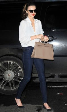 Miranda Kerr looked classically casual and elegant in skinny indigo wash jeans, a white blouse and a pale mushroom bag.