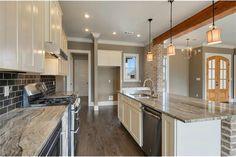 Gorgeous contrasting tile backsplash, granite countertops & reclaimed cypress beams in kitchen.